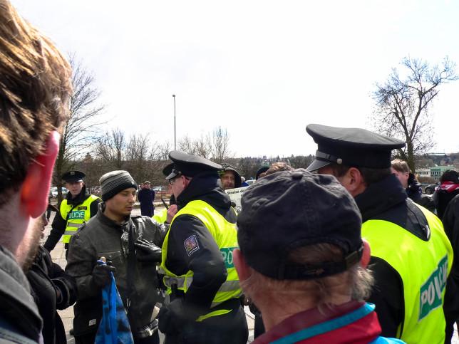Policisté s mladíkem, který měl vlajku USA ozdobenou hákovým křížem